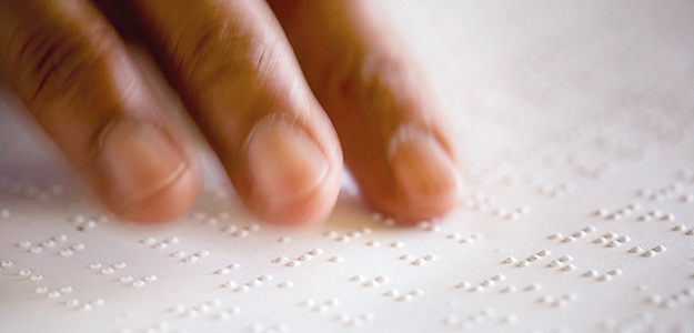 Finger eines Sehbehinderten erfühlen die Braille-Schrift.